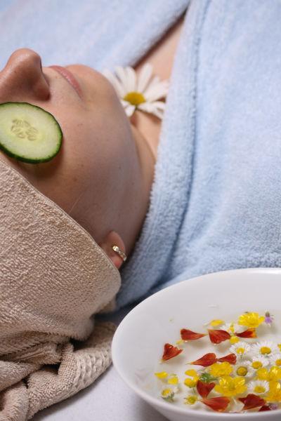 Une femme se détend en peignoir avec des rondelles de concombre sur les yeux